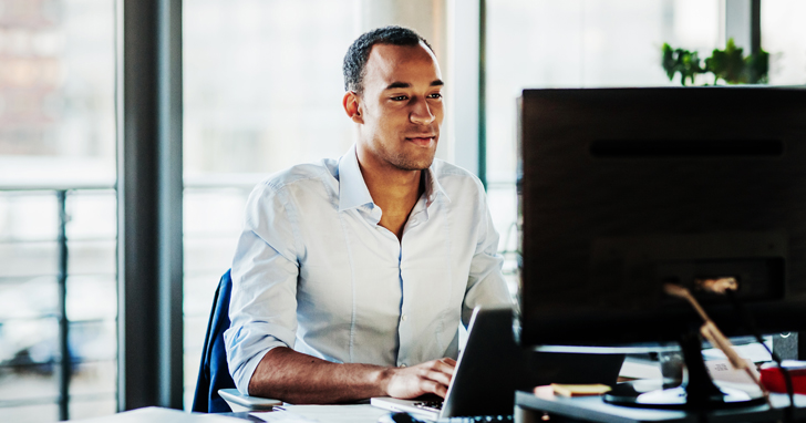 man sits at desk and uses computer