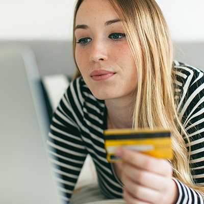 Woman shopping with check or credit card online