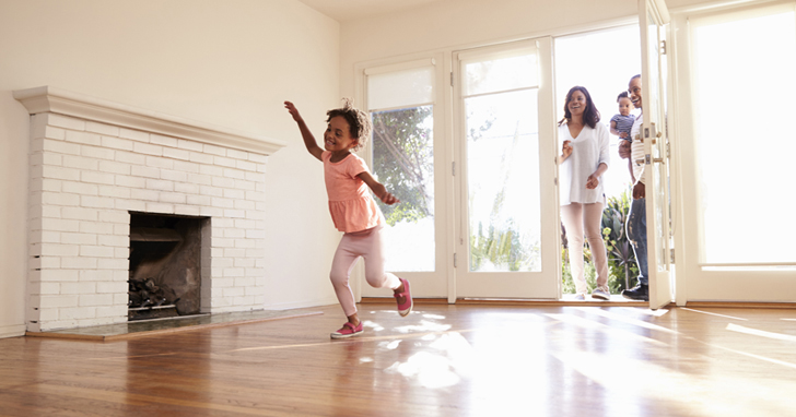 Child dances in empty living room beside fireplace while parents watch in doorway
