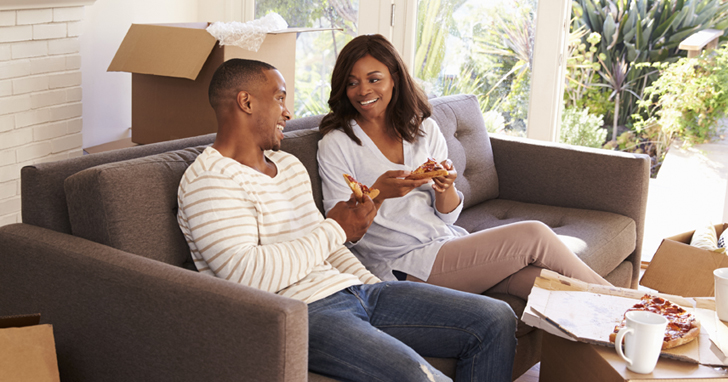 Couple eating pizza while sitting on sofa with moving boxes in background