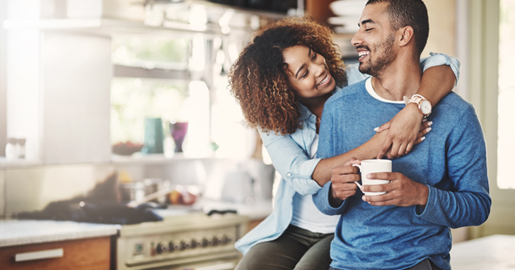 African-American couple drinking coffee in kitchen