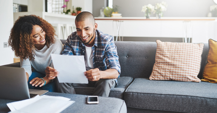 Man and woman sit on couch and read in front of laptop