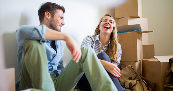 Young couple laughing with moving boxes in background