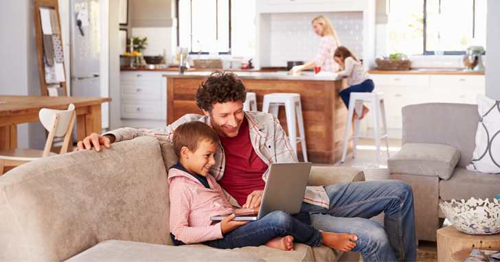 father and son sit on couch and use laptop computer