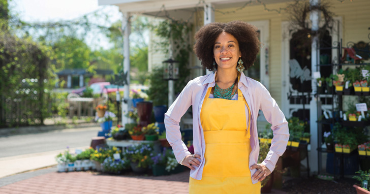 Woman standing proudly in front of her business
