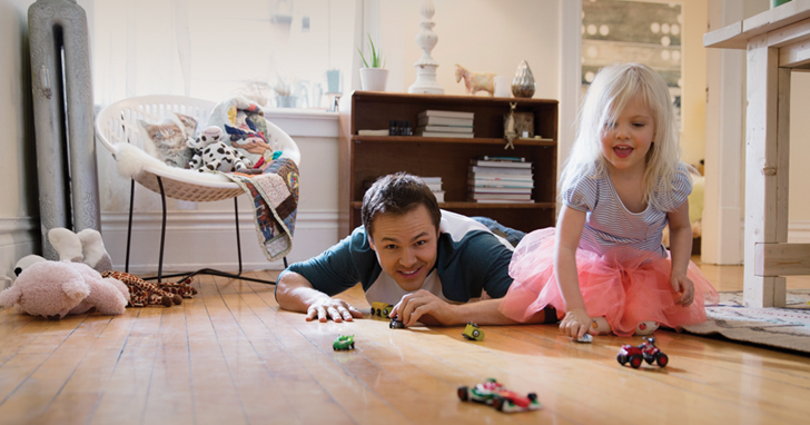 Man plays with his daughter on the floor with toys